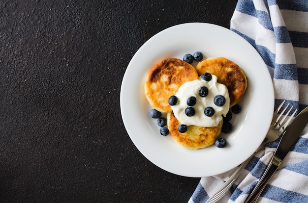 Panquecas de queijo no café da manhã com creme de leite ou iogurte e mirtilo. Foto Premium