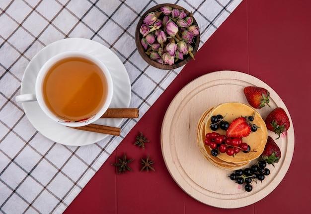 Panquecas de vista superior com passas de corinto vermelhas e pretas e morangos em uma bandeja com uma xícara de chá e canela em um fundo vermelho Foto gratuita