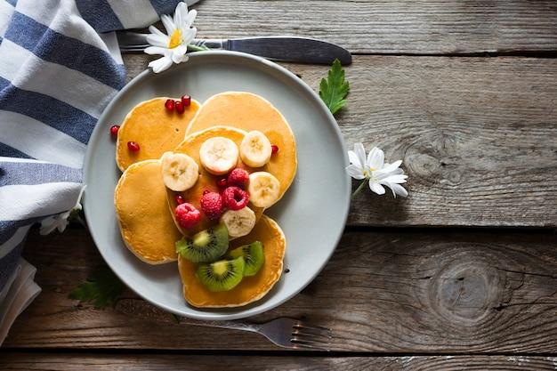 Panquecas planas leigos com mistura de frutas Foto gratuita