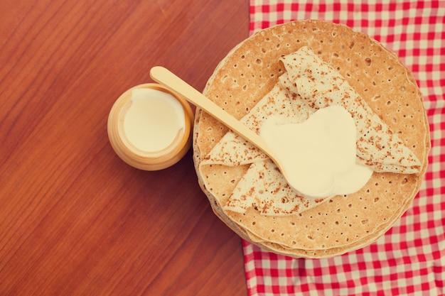 Panquecas russas ou blini com creme de leite. vista do topo. semana da panqueca. entrudo. espaço para texto Foto Premium