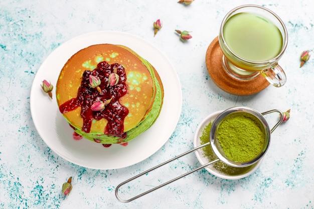 Panquecas verdes com matcha em pó com geléia vermelha, vista superior Foto gratuita