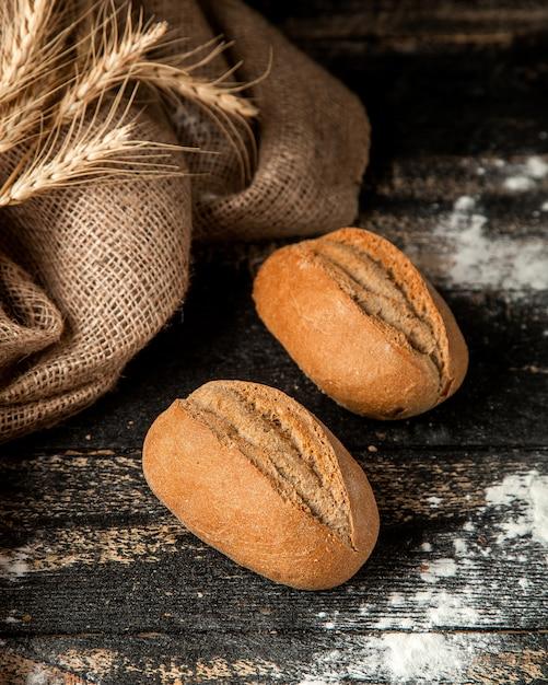 Pão baton com crosta crocante e farinha na mesa Foto gratuita
