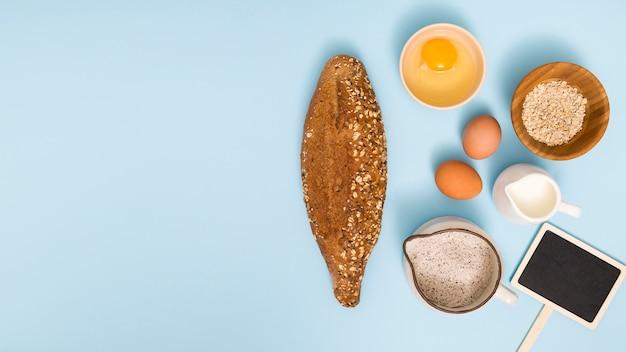 Pão caseiro; ovo; celeiro de aveia; leite; farinha e letreiro sobre fundo azul Foto gratuita