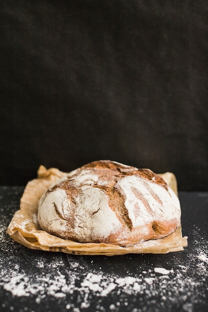 Pão caseiro rústico no papel marrom contra o fundo preto Foto gratuita