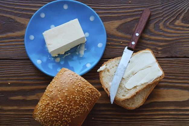 Pão com gergelim e manteiga em uma mesa de madeira rústica. fazendo torradas e sanduíches para café da manhã ou almoço. Foto Premium