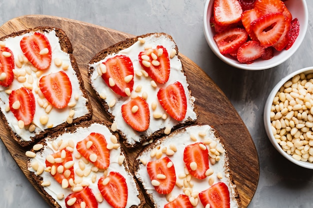 Pão com morango, pinhões e cream cheese em fundo cinza Foto Premium