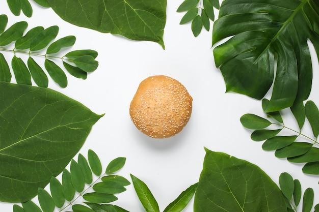 Pão com sementes de gergelim em um fundo branco com folhas tropicais verdes Foto Premium
