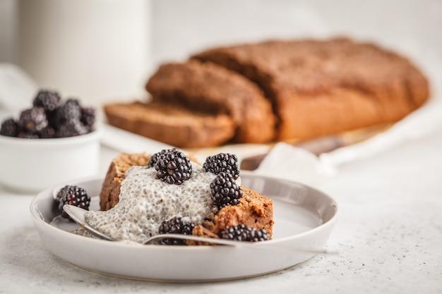 Pão de banana do vegetariano do chocolate com pudim e amoras-pretas, fundo branco do chia. Foto Premium