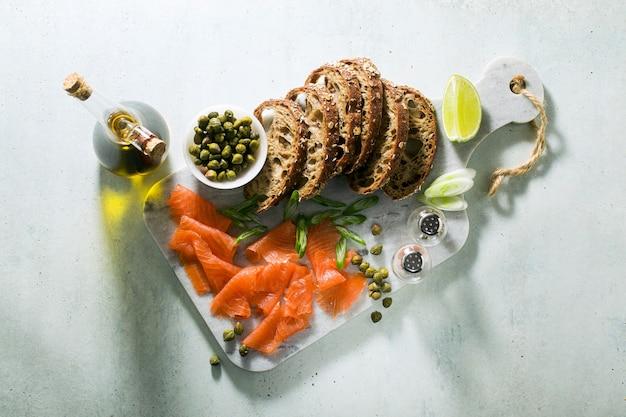 Pão de centeio com salmão defumado na placa de mármore. lanche de inverno. Foto Premium