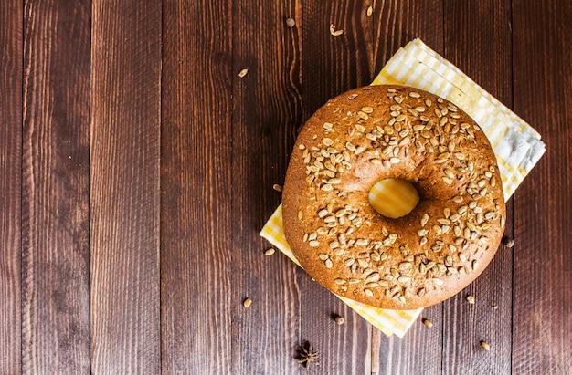 Pão de centeio com sementes de girassol na toalha na placa de madeira Foto gratuita