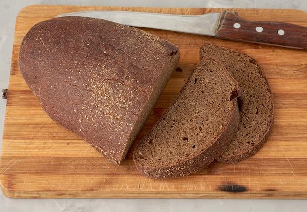 Pão de centeio oval fatiado em uma placa de madeira Foto Premium