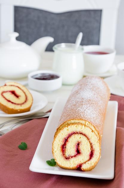 Pão de ló caseiro com geléia de framboesa em um prato branco sobre uma mesa de jantar de madeira branca com uma xícara de chá de baga perfumado. Foto Premium