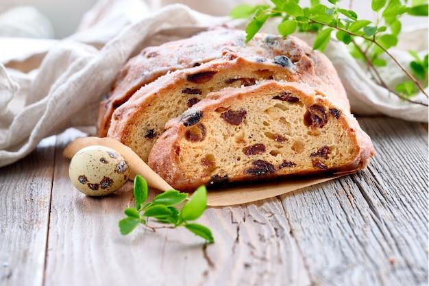 Pão de páscoa, close-up no pão fruty tradicional em madeira rústica com folhas frescas e ovo de codorna Foto Premium
