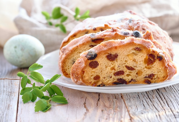 Pão de páscoa, close-up no pão fruty tradicional em madeira rústica com folhas frescas e ovo pintado Foto Premium