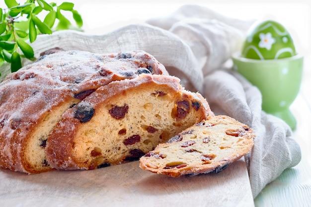 Pão de páscoa, closeup no pão fruty tradicional em madeira rústica com folhas frescas e ovo pintado Foto Premium