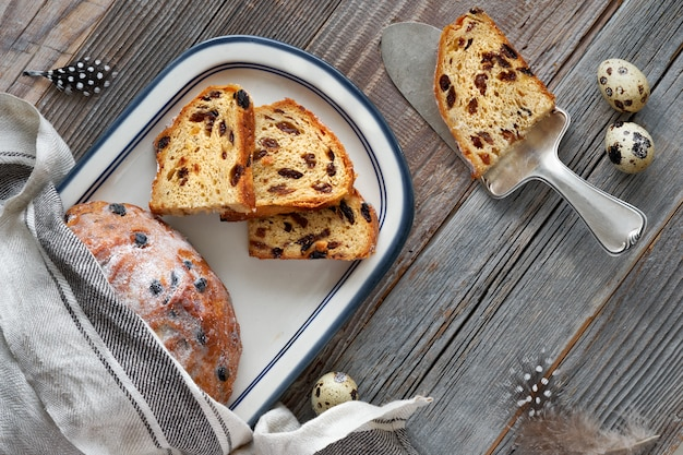 Pão de páscoa (osterbrot em alemão). vista superior do pão frutado tradicional em madeira rústica com folhas frescas e ovos de codorna Foto Premium