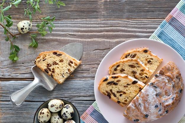 Pão de páscoa (osterbrot em alemão). vista superior do pão fruty tradicional na mesa de madeira rústica com folhas frescas e ovos de codorna. Foto Premium
