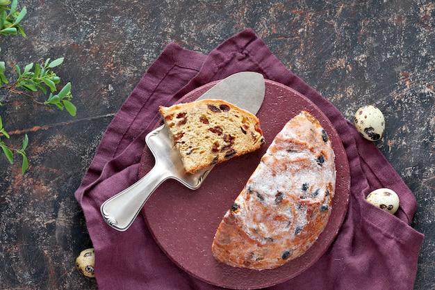 Pão de páscoa (osterbrot em alemão). vista superior do pão fruty tradicional na mesa escura com folhas frescas e ovos de codorna Foto Premium