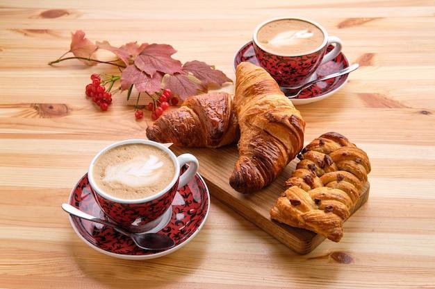 Pão de passas de massa folhada e croissant crocante na mesa de madeira com café Foto Premium