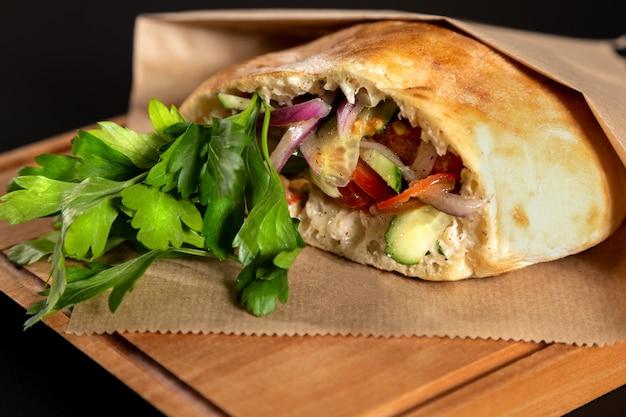 Pão de pita com legumes na mesa de madeira em fundo preto Foto Premium