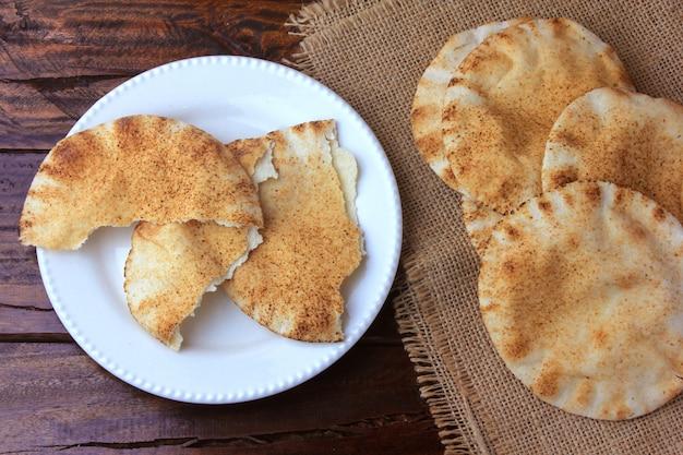 Pão de pita isolado na mesa de madeira rústica em pano rústico Foto Premium