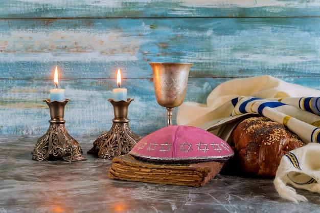 Pão de shabat shabat, vinho de shabat e velas em cima da mesa. vista do topo Foto Premium