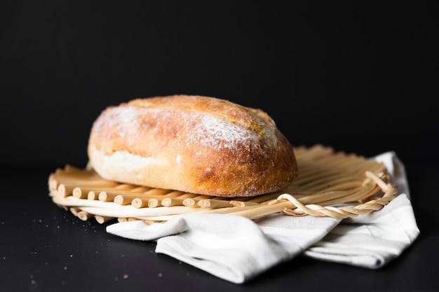 Pão delicioso tamanho inteiro em material de pano e fundo preto Foto gratuita