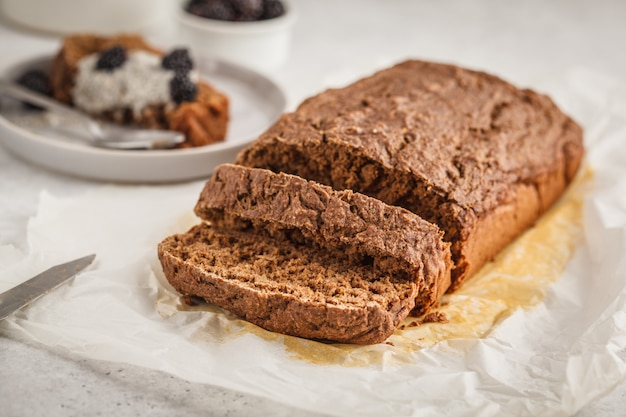 Pão do abobrinha do vegetariano do chocolate com pudim do chia e amoras-pretas, fundo branco. Foto Premium