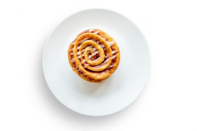 Pão doce com rolo de canela colocado em um prato branco isolado em um fundo branco. Foto Premium