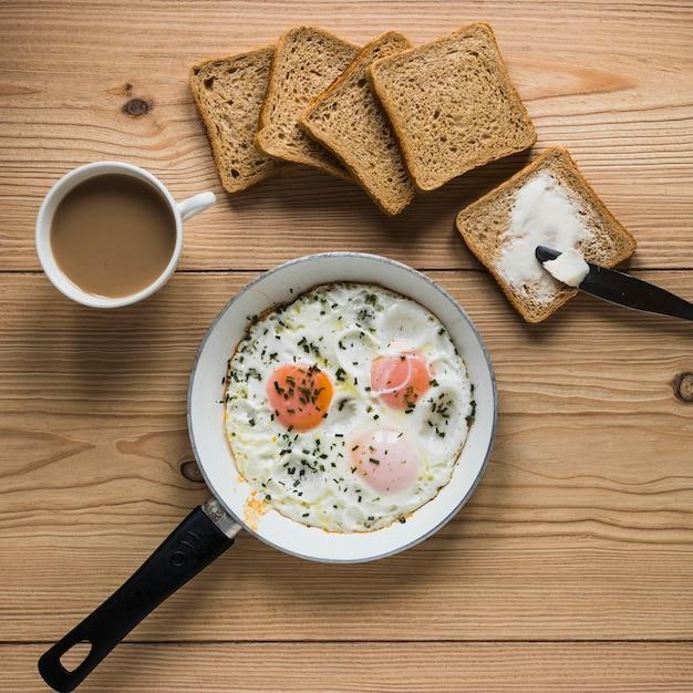 Pão e café perto de ovos fritos Foto gratuita