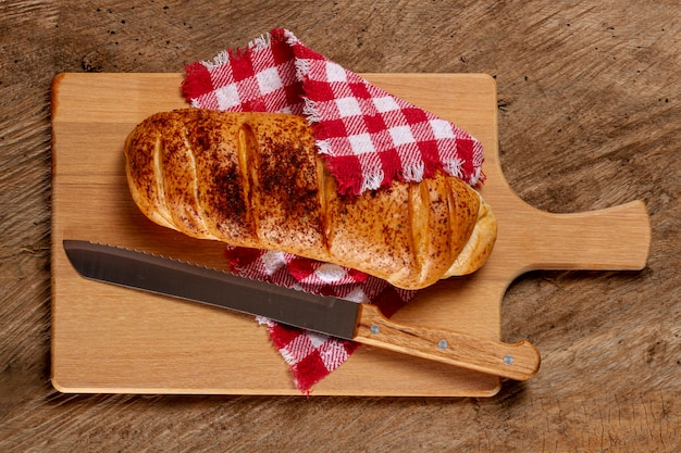 Pão e faca na placa de madeira Foto gratuita