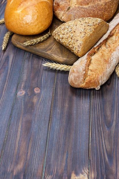 Pão e trigo no fundo de madeira. vista superior com espaço de cópia Foto Premium