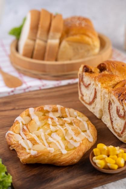 Pão em uma bandeja de madeira em um pano vermelho e branco. Foto gratuita