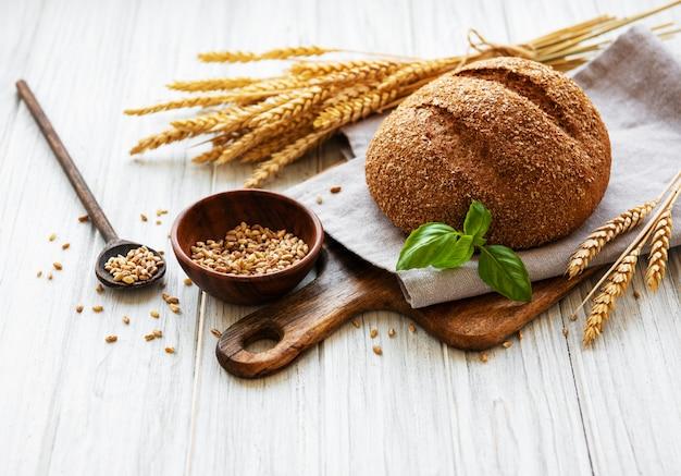 Pão em uma velha mesa de madeira branca Foto Premium