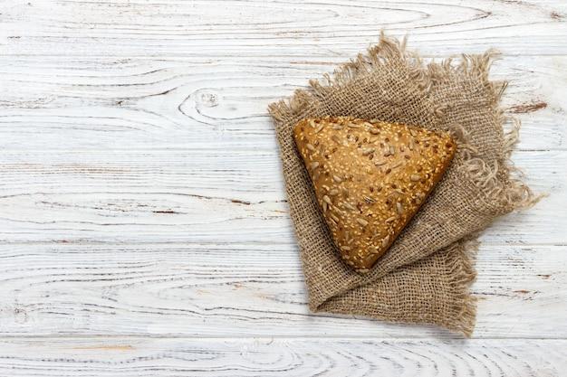 Pão fresco ou pão com gergelim e sementes de girassol na mesa de madeira Foto Premium