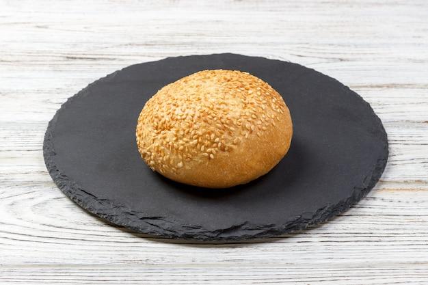 Pão fresco ou pão com gergelim e sementes de girassol na placa de ardósia Foto Premium