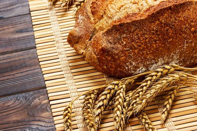Pão integral caseiro fresco com trigo em um fundo de madeira Foto Premium