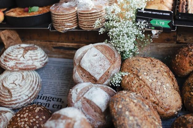 Pão integral com pães rústicos e flores brancas Foto gratuita