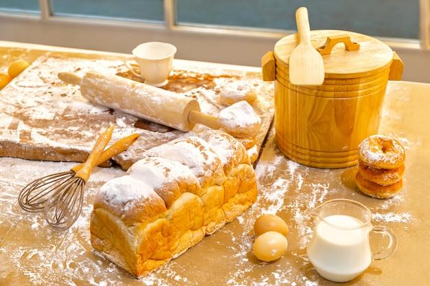 Pão, ovos, leite, donuts e leite fresco na mesa de madeira perto da janela. preparatório de café da manhã Foto Premium