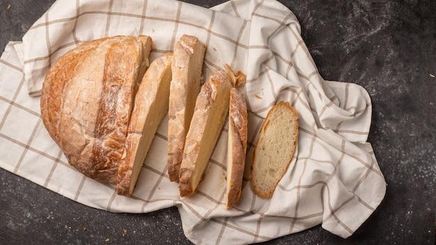 Pão redondo branco cortado em vários pedaços, localizado com um guardanapo xadrez branco no preto Foto Premium