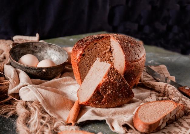 Pão redondo e fatiado inteiro em uma mesa de cozinha de pedra com ovos e faca. Foto gratuita