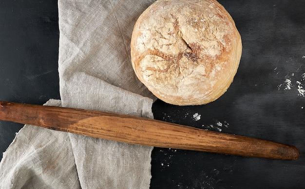 Pão redondo e velho rolo de madeira sobre uma mesa preta Foto Premium