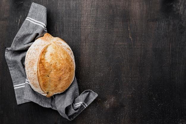 Pão redondo em pano com fundo de madeira de espaço de cópia Foto gratuita