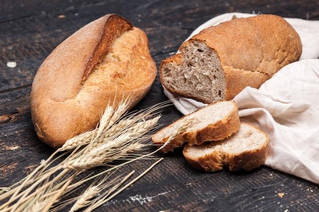 Pão rústico na mesa de madeira. fundo de madeira escuro Foto gratuita