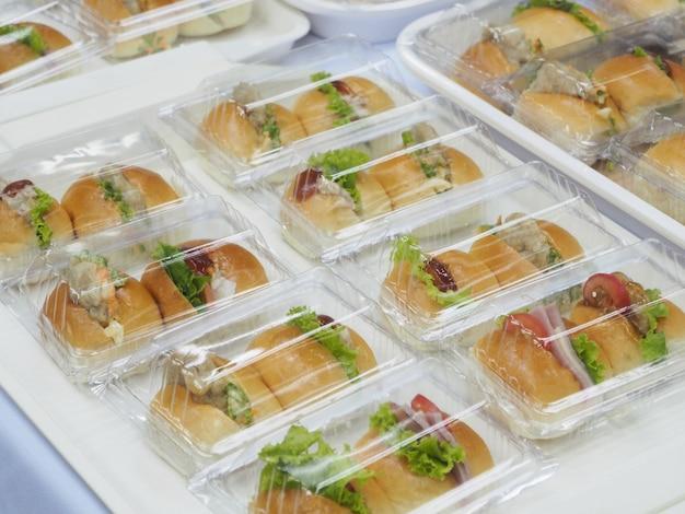 Pão, salada e pacote de carne de porco em caixa de plástico, para o intervalo de reunião. Foto Premium