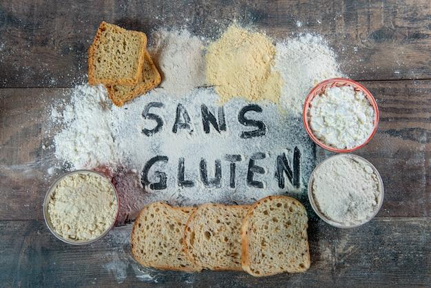 Pão sem glúten (sem glúten) e farinha no fundo de madeira Foto Premium