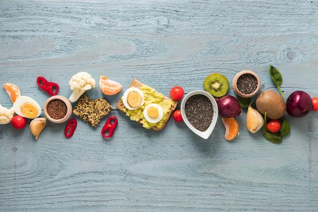 Pão torrado; frutas frescas e ingredientes dispostos em uma linha na mesa de madeira Foto gratuita