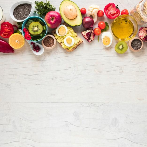 Pão torrado; frutas frescas; legumes e ingredientes dispostos na mesa Foto gratuita