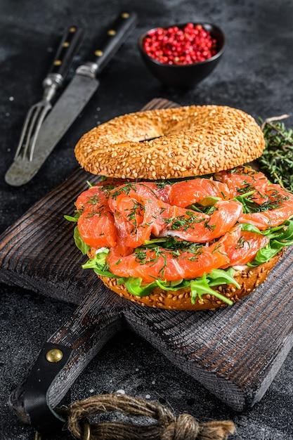 Pãozinho de salmão defumado com queijo macio, rúcula em uma tábua de madeira. fundo preto. vista do topo. Foto Premium