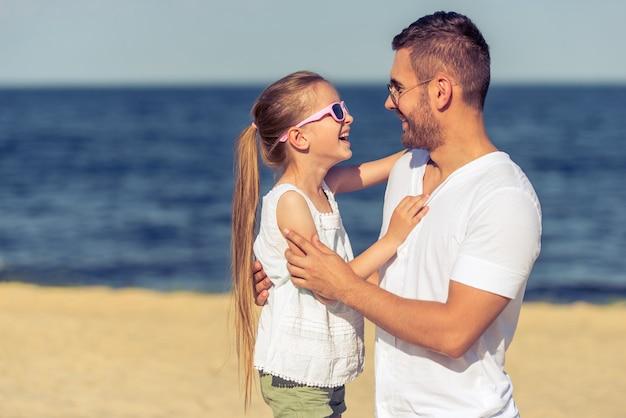 Papai e sua filha em óculos de sol estão sorrindo. Foto Premium